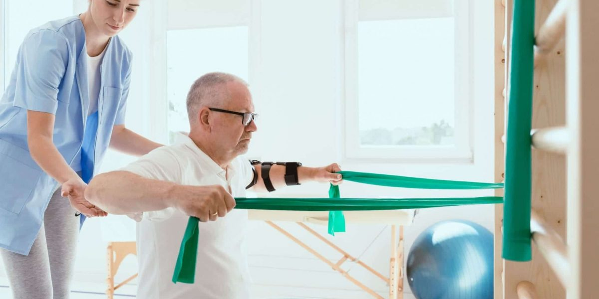 elderly-man-doing-gymnastic-exercises-with-a-young-9LW2XH6